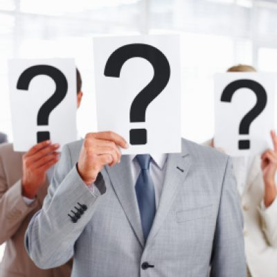 Group of business people covering their faces with question mark